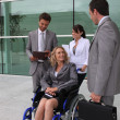 Businesswoman in a wheelchair with colleagues outside an office building — Stock Photo