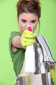 Girl holding detergent with pistol pump against green background — Stock Photo