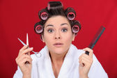Woman with her hair in curlers holding scissors and a comb — Stock Photo