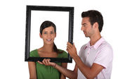 Attractive couple with frame — Stock Photo
