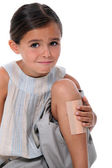 Young girl with an enormous plaster on her leg — Stock Photo