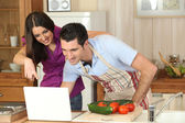 Couple following a recipe on a laptop — Stock Photo