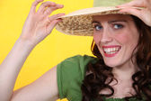 Woman with a straw hat and a toothy grin — Stock Photo