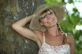Summery woman standing by a tree — Stock Photo