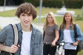 Jovem na frente de duas garotas com motos — Foto Stock