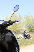 Couple relaxing in a park next to their scooter — Stock Photo