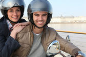 Couple riding scooter together — Stock Photo