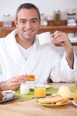 Man having breakfast in dressing gown — Stock Photo