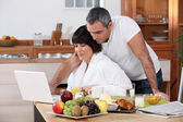 Couple looking at their laptop during breakfast — Stock Photo