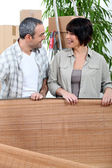 Couple unrolling a mat in their new home — Stock Photo