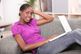 Young woman lying on a sofa with a laptop computer — Stock Photo