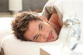 目を覚ますベッドの中で若い男 — ストック写真