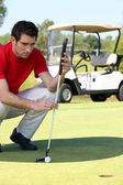 Golfer crouched next to the hole — Stock Photo