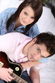 A young couple on bed, the man is playing guitar — Stock Photo