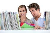 A couple of students at the library. — Stock Photo
