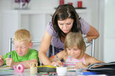 Mother helping her kids with the homework — Stock Photo