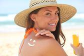 Kvinna använda solkräm på stranden — Stockfoto