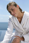 Woman sat at the seaside in white robe — Stock Photo