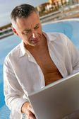 Man sitting at a poolside in front of a laptop computer — Stock Photo