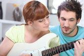 Homem ensinando uma mulher a tocar violão — Foto Stock