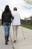 Young woman helping elderly lady walk — Stockfoto