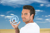 Man holding the at symbol — Stock Photo