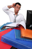 Office worker surrounded by paperwork — ストック写真