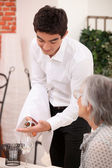 Young waiter serving an older customer rose wine — Stock Photo
