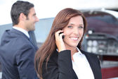Businesswoman on the phone and businessman in the background — Stock Photo