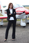 Jonge vrouw staande voor een vliegtuig — Stockfoto