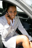 Businesswoman sat in car with mobile — Stock Photo