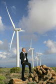 Man using a mobile phone next to wind turbines — Stock Photo