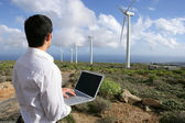 Man with laptop in wind farm — Stock Photo
