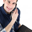Stock Photo: Handsome mlistening to voice message