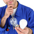 Electrician holding light bulbs - Stock Photo