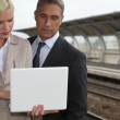 Business couple with a laptop on a railway platform — Stock Photo