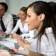 Woman using a calculator at an office team meeting — Stock Photo #8665437