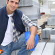 Worker posing with stacks of concrete blocks - Stock Photo