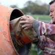 Man putting cement in a mixer - Stock Photo