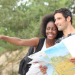 Couple reading map outdoors — Stockfoto