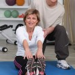A senior woman doing floor exercises with a coach — Stock Photo