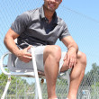Smiling friendly tennis umpire sitting in the sunshine - Stock Photo