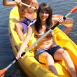 Girl and boy canoeing together — Stock Photo #8668129