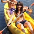 Girl and boy canoeing together - Stock Photo