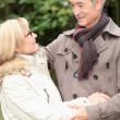 Stock Photo: Older couple embracing on winter's stroll