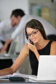 Brunette sat at desk working — Stock Photo