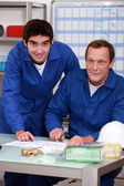Two factory workers checking inventory — Stock Photo