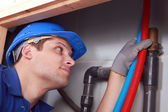 Plumber with hot and cold flexible water pipes — Stock Photo