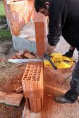 Man using a chainsaw to cut through a brick — Stock Photo