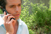 Man on the phone outdoors looking concerned — Stock Photo